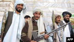 Surrendering Taliban militant fighters stand with their weapons as they are presented to the media at a government building in Herat in November 2008.