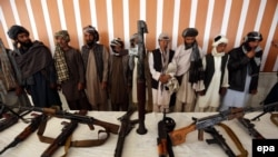 Former Taliban militants surrender arms in the western Afghan city of Herat.
