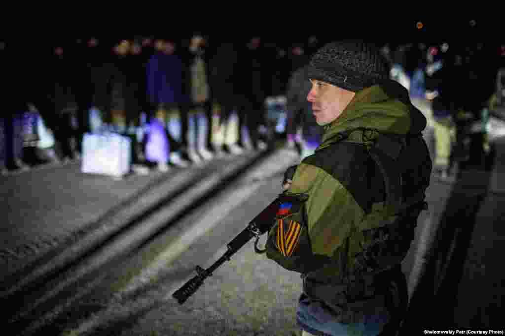 Проросійский бойовик охороняє колону українських полонених під час процедури обміну
