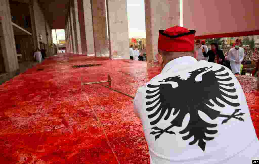 A chef cuts a huge cake, with the Albanian flag symbols, measuring 550 square meters, on the main boulevard of Tirana, Albania, during centenary celebrations on November 28. (AFP/Gent Shkullaku)