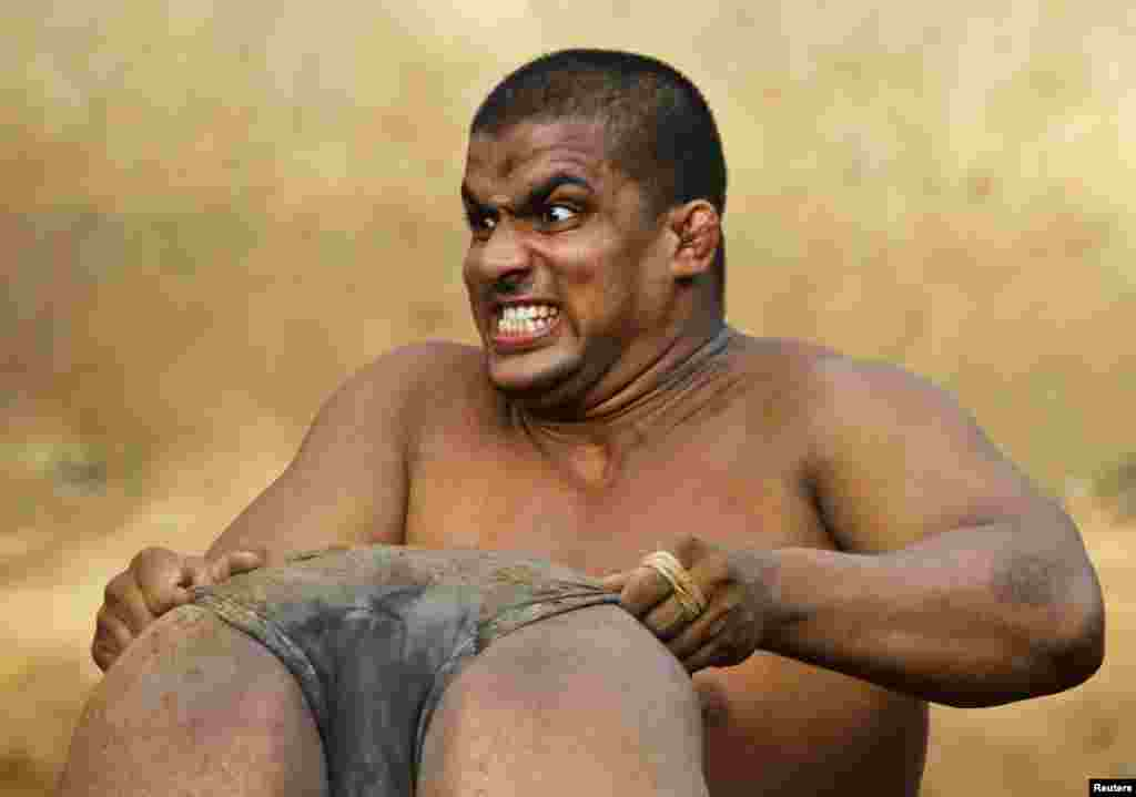 A wrestler reacts as he lifts his colleague in the mud at an Indian Kushti mud-wrestling training center on the outskirts of New Delhi on June 13. Kushti is a traditional sport in India but more and more young athletes are now training on mats instead of mud to gain access to top international competitions like the Olympic and Commonwealth games. (Reuters/Parivartan Sharma)
