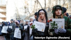 People hold posters with names of the people killed in the Ukraine International Airlines plane that was shot down in Iran in January during a commemoration ceremony in front of the Iranian Embassy in Kyiv on February 17.