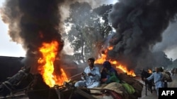 Local residents pass beside burning NATO oil tankers following an attack by the Taliban in Nowshera, Pakistan