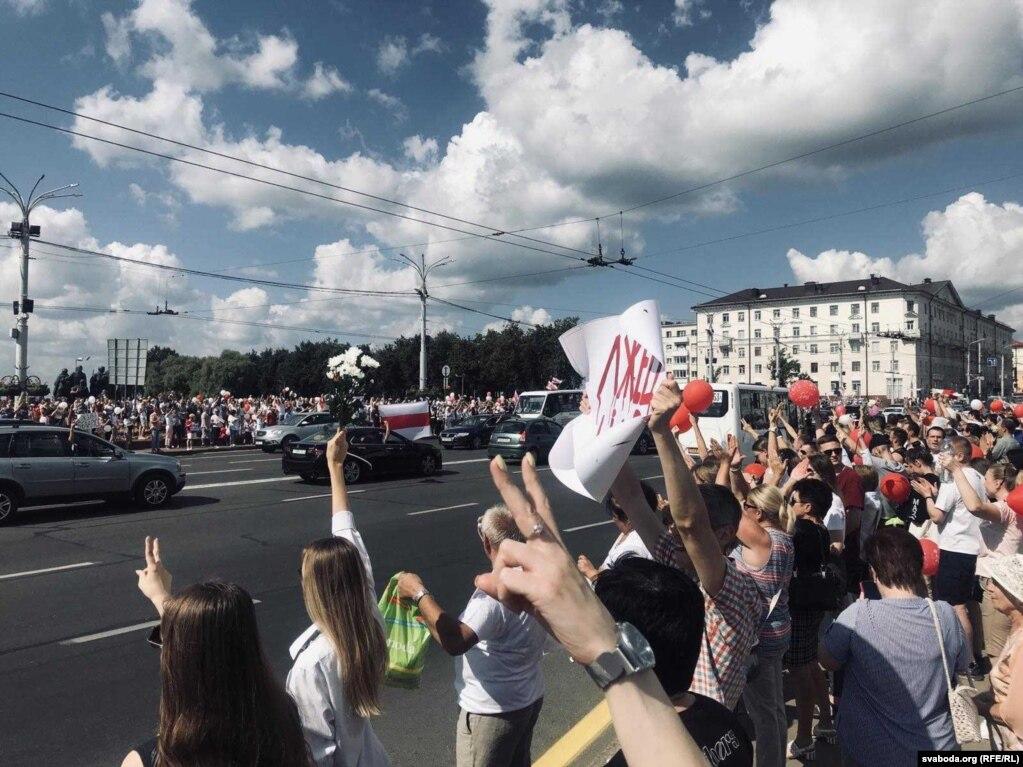 Hunderte von Menschen mit Blumen, Luftballons und weiß-rot-weißen Flaggen marschierten zum Siegesplatz in Minsk