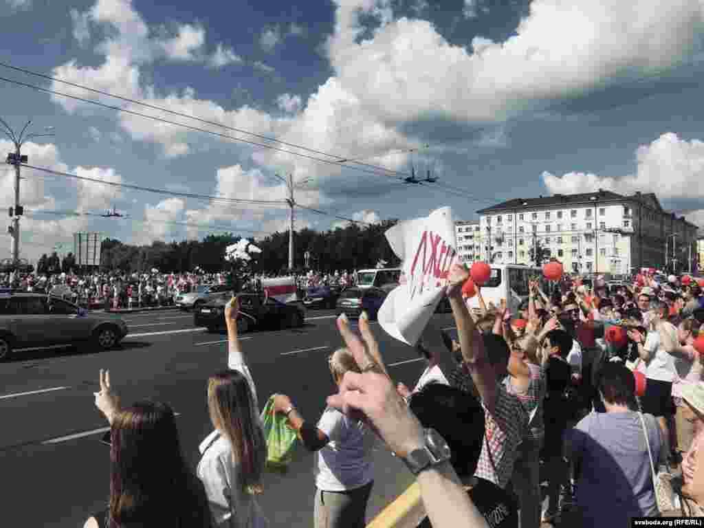 Сотні людей з квітами, повітряними кульками та біло-червоно-білими прапорами йшли до площі Перемоги в Мінську