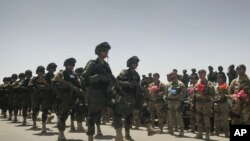 Afghan troops pass by Italian soldiers from the NATO-led International Security Assistance Force (ISAF) during the transfer of authority to Afghan security forces in Herat last July.