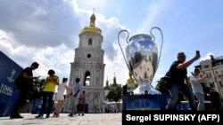 Туристы фотографируются на фоне инсталляции кубка Лиги чемпионов в Киеве, 25 мая 2018 года