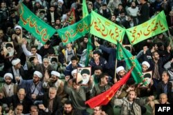 Iranians chant slogans as they march in support of the government near the Imam Khomeini grand mosque in the capital, Tehran, on December 30.