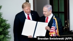 U.S. President Donald Trump (left) and Israeli Prime Minister Benjamin Netanyahu hold up the Golan Heights proclamation after a meeting in the the White House in Washington on March 25.