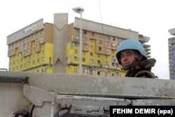 A soldier with the NATO-led multinational Implementation Force (IFOR) stands watch with the badly hit Holiday Inn hotel in the background in December 1995.