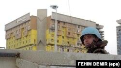 Војник на ИФОР (сили за спроведување) го надгледува градот со лхотел Холидеј Ин во позадина во Сараево, Босна и Херцеговина, 14 декември 1995 година.
