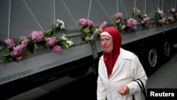 A woman cries near a truck carrying coffins of newly identified victims of the 1995 Srebrenica massacre, in Sarajevo, July 9, 2015.