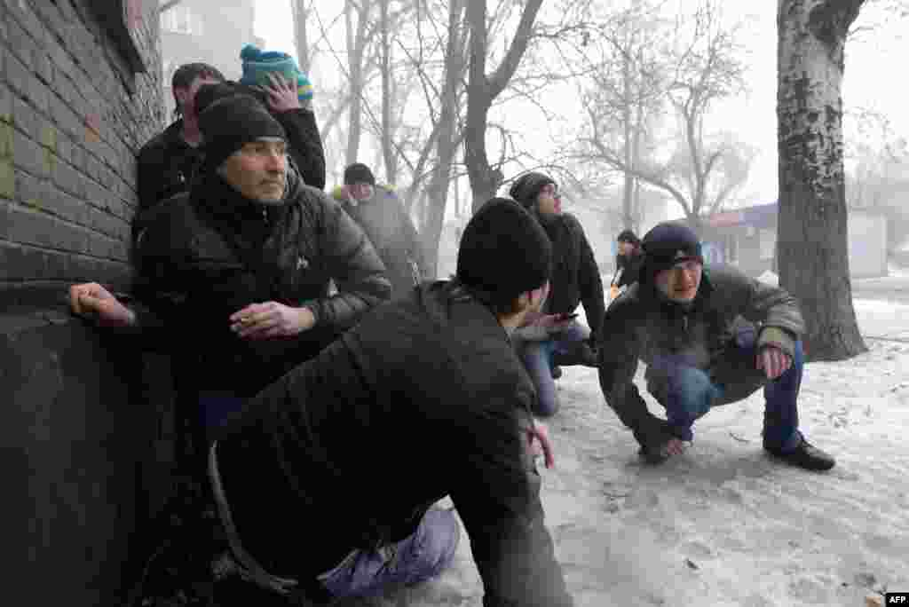People take cover during shelling in Donetsk.
