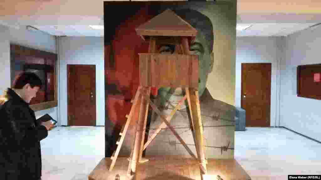 """Мұражай қабырғасына ілінген совет диктаторы Иосиф Сталиннің фотопортретіне тікенек сыммен оралған күзетші мұнарасы әдейі тақап қойылған. Мұражай қызметкерлерінің айтуынша, бұл суретке қай бұрыштан қарасаңыз да """"Сталиннің кірпік қақпай сізді қадағалап тұрғанын байқайсыз""""."""