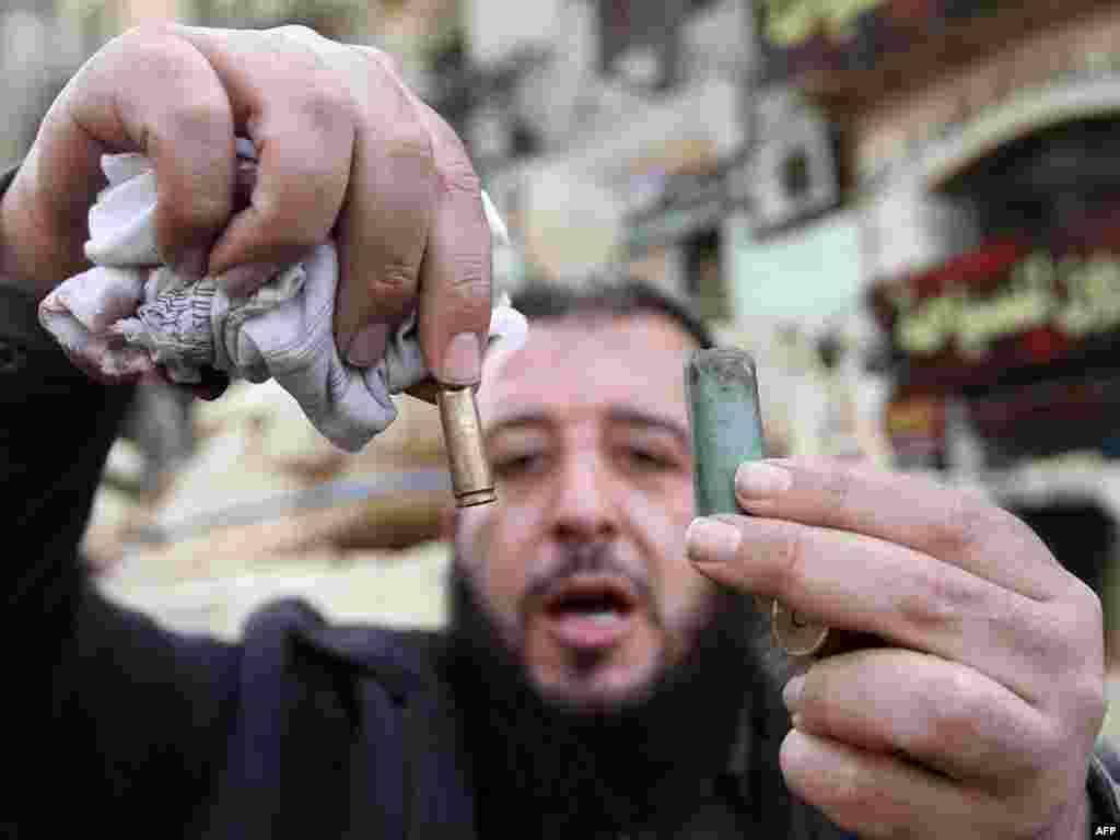 Бер демонстрацияче Каһирә үзәгендәге Тәхрир мәйданында полиция ут ачканнан соң калган әйберләрне күрсәтә. 29 гыйнвар 2011.