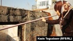 Шынара Бисенбаева, жена Саяна Хайрова, возле разрушенного дома, в котором в августе 2012 года погиб ее сын Ислам. Поселок Баганашыл Алматинской области, 14 ноября 2013 года.