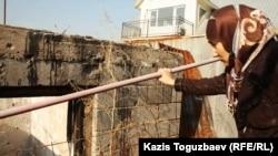 Шынара Бисенбаева, жена осужденного по обвинению в религиозном экстремизме Саяна Хайрова, стоит возле разрушенного дома, в котором в августе 2012 года в ходе спецоперации против вооруженной группировки погиб ее сын Ислам. Поселок Баганашыл Карасайского района Алматинской области, 14 ноября 2013 года.