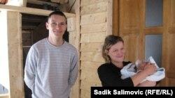 """Almir i Dušica Salihović sa sinom Jusufom ispred kućice koju im je sagradila austrijska organizacija """"Seljaci pomažu seljacima"""""""