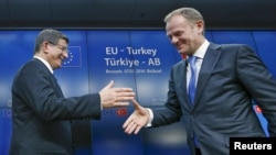 Turkish Prime Minister Ahmet Davutoglu (left) shakes hands with European Council President Donald Tusk after meeting to discuss Europe's migrant crisis. Turkey's neighbors fear that, if Ankara toughens its visa regime to help stem the flow of migrants into Europe, it could also drastically reduce the number of countries whose citizens can currently enter Turkey easily.