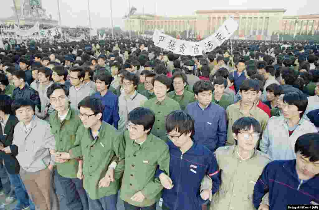 Chinese students link arms in solidarity at dawn on Saturday, April 22, 1989 in Beijing�s Tiananmen Square after spending the night there in order to be on hand for memorial services for the late purged party chief Hu Yaobang. The students defied warnings against demonstrating and gathered by the tens of thousands forcing officials to back down and allow them to stay. (AP Photo/Sadayuki Mikami)