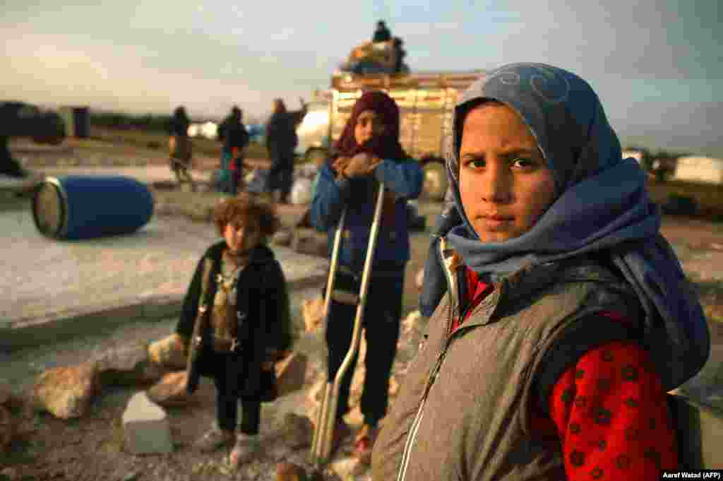 Syrian children pose for a picture as their families prepare to flee a camp for the displaced east of Sarmada, which lies north of Idlib Province. (AFP/Aaref Watad)