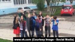 Фотография, на которой школьники вскидывают руки