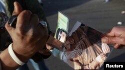бунтовник ја расекува фотографијата на лидерот Муамар Гадафи
