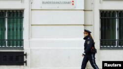 FILE: A police officer walks in front of the Austrian chancellery in Vienna.