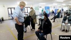 Boris Johnson brit miniszterelnök Covid-oltásra váró emberekkel beszélget Batley városában, 2021. február 1-én.