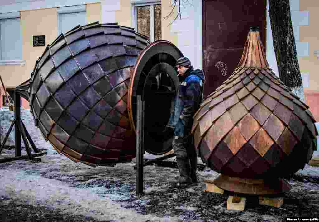 A worker stands next to two metal onion domes during the renovation of a church in the historical center of Yaroslavl, Russia. (AFP/Mladen Antonov)