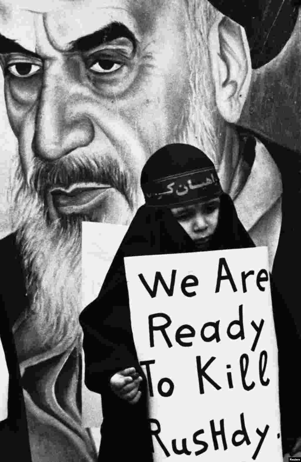 A black-clad girl carries a sign vowing to kill Rusdie during a pro-Iranian rally in Beirut's southern suburb one month after the Khomeini fatwa. (Reuters/stringer)