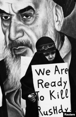 """İran, 26 fevral, 1989. Qızın əlindəki plakatda """"Biz Salman Rushdie-ni öldürməyə hazırıq"""" yazılıb."""