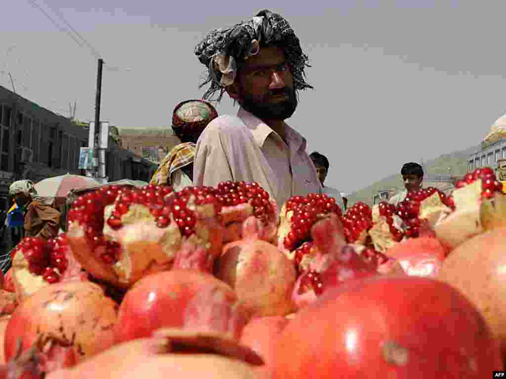 "An Afghan pomegranate vendor waits for customers in Kabul on August 24. A report by the office of the UN High Commissioner for Human Rights claims that over a third of Afghans live in ""absolute poverty"" and about the same number are only slightly above the poverty line. It blamed corruption in Afghanistan, and the international community for ignoring the basic needs of people. Photo by Shah Marai for AFP"