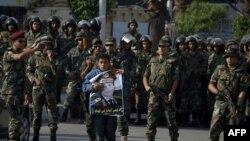 Коргоо министри, генерал Абдел Фаттах ал-Сисинин портретин көтөргөн адам Каирдин чыгышындагы Наср Сити районунда аскерлердин арасында турат. 11-октябрь 2013