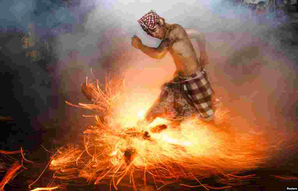 A Balinese man kicks up fire during the Perang Api ritual ahead of Nyepi day, on the island of Bali. Nyepi is a day of silence for self-reflection to celebrate the Balinese Hindu new year, where Hindus in Bali observe meditation and fasting but are not allowed to work, cook, light lamps, or conduct any other activities. (Reuters)