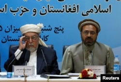 Mohammad Amin Karim (right), a representative of Gulbuddin Hekmatyar, and Sayed Ahmad Gilani, the head of the government's High Peace Council, speak after signing a peace deal in Kabul on September 22.