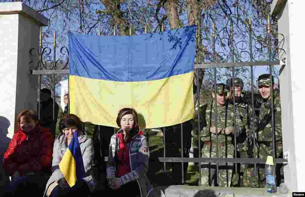 У селищі Любимівка українські військовослужбовці збираються на території військової частини. Їхні родичі сидять біля паркану, щоб не допустити збройних зіткнень. 3 березня 2014 року