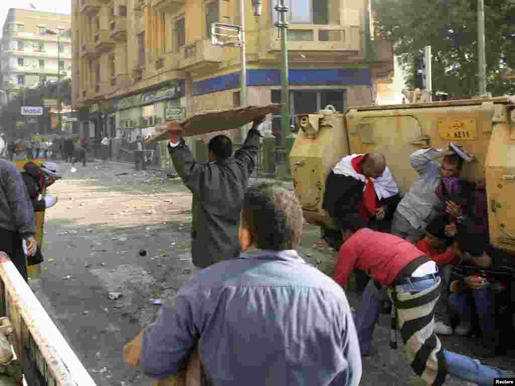 Demonstrators take cover during rioting between pro- and anti-Mubarak demonstrators in Tahrir Square.