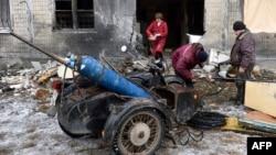 Зварювальники ремонтують трубу ззовні квартири, яка була зруйнована внаслідок бойових дій. Донецьк. 8 грудня 2014 року