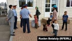 Женщина-репатриант Женисгуль Ермухамет вместе с детьми у здания резиденции президента Казахстана. Астана. 29 июля 2015 года.