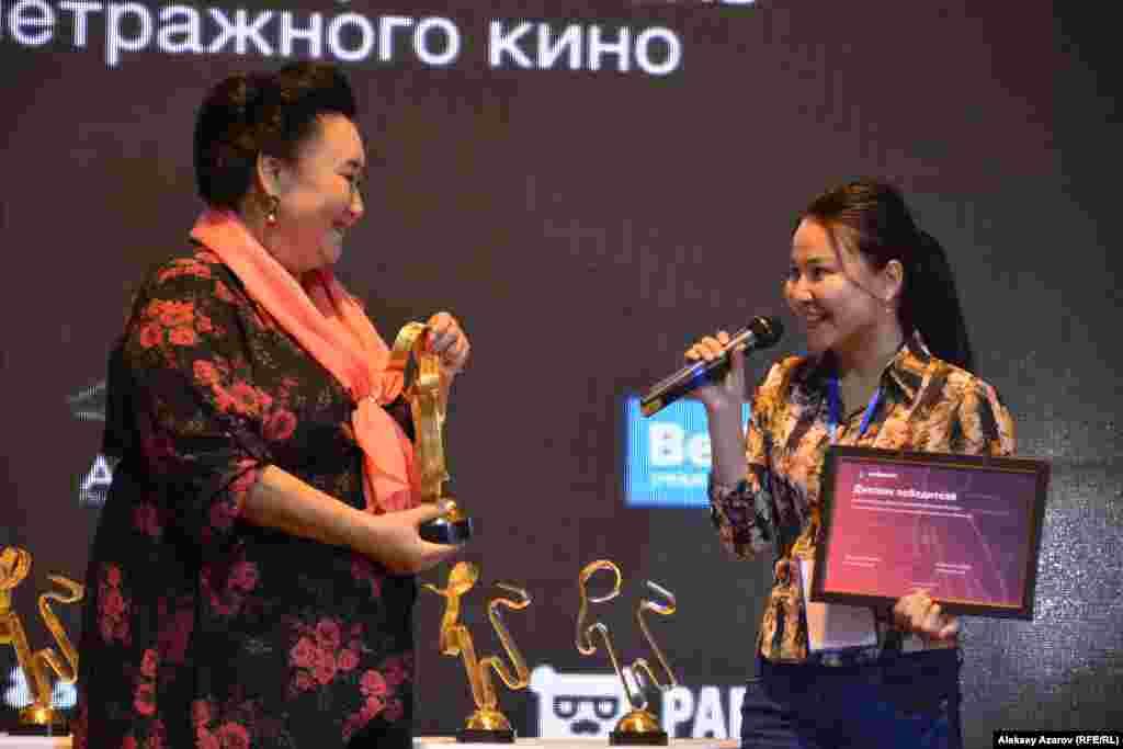 Кымбат Тойшы (справа) получает из рук Гульнары Абикеевой приз в номинации «Лучший документальный фильм» за работу «Ауыл тынысы» («Дыхание аула»), рассказывающую о семье фермера.