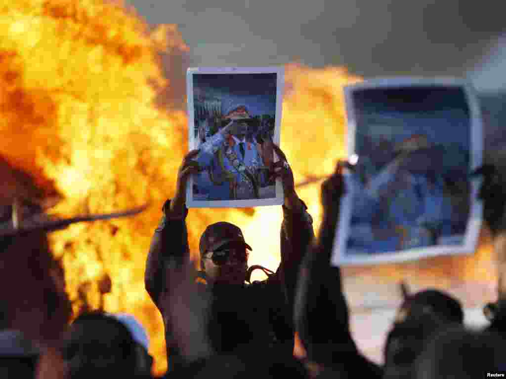 Men hold up posters of Libyan leader Muammar Qaddafi as a fuel truck burns in Tripoli on March 2. Photo by Chris Helgren for Reuters