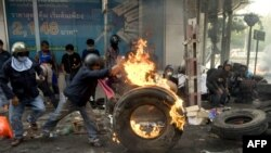 A demonstrator pushes a burning tire during clashes with security forces in Bangkok on May 15.
