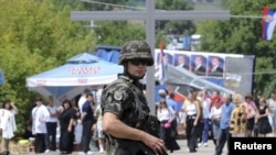 A Slovenian KFOR soldier stands on a road in front of barricades in the village of Rudare, in northern Kosovo, on August 5.