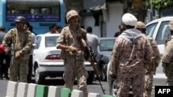 Members of the Islamic Revolutionary Guards Corps secure the area outside the Iranian parliament during an attack on the complex in Tehran on June 7.