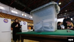 A woman holds a ballot paper at a voting center in Pristina, Kosovo.