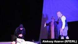 Эпизод из спектакля. Лангман, вдова над убитым им носильщиком. Нефть изображена в виде автомобильной покрышки. Алматы, 23 июня 2018 года.