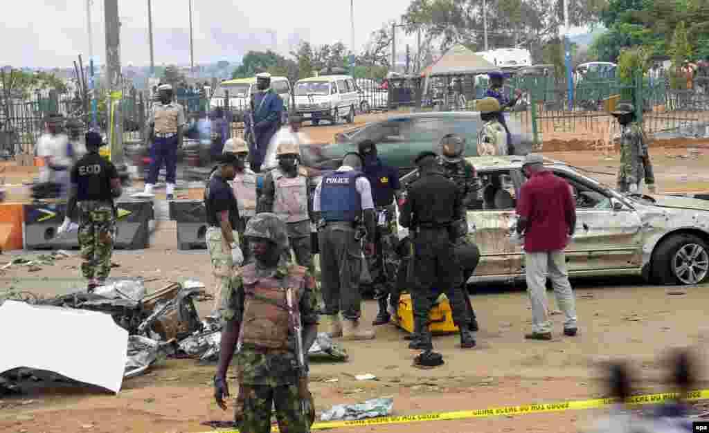 """5 мамыр күні кешке Нигериядағы """"Боко харам"""" қарулы тобы елдің солтүстік-шығысындағыГамбору-Нгала қаласына шабуыл жасап, бейбіт тұрғындарды атып, үйлер мен дүкендерді өртеген. Ақпараттарға қарағанда, 12 сағатқа жалғасқан шабуыл салдарынан 300-дей адам опат болған.""""Боко харам"""" қарулыисламшылар тобы кейінгі уақытта Нигериядабірнеше қанды шабуыл ұйымдастырды. Суретте: Автокөлікке орнатылған бомба жарылған жерді зерттеп жүрген ресми адамдар. Абуджа, Нигерия, 2 мамыр 2014 жыл."""