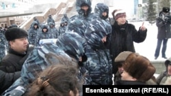 Mortgage holders and investors are met by security forces in Almaty on March 15.
