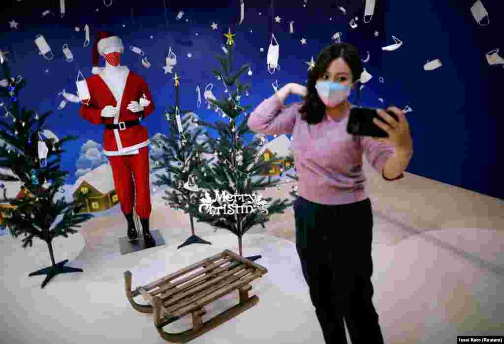 Жінка намагається зробити селфі перед вітриною з різдвяними декораціями та масками у спеціалізованій крамниці в Tokyo Mask Land. Йокогама, Японія